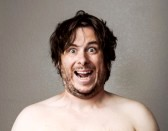 14944837-topless-man-making-a-creepy-looking-smile-at-the-camera-against-a-lightly-textured-background